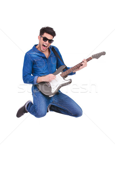 screaming guitarist jumps while playing his electric guitar Stock photo © feedough
