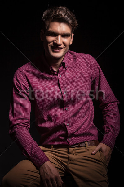 Young man sitting with his hand in pocket. Stock photo © feedough