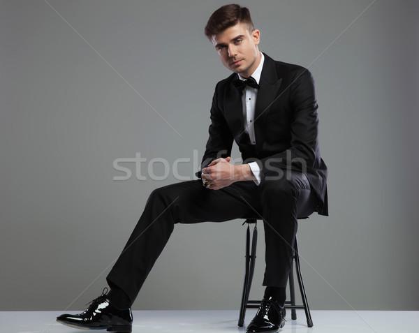 elegant young man in tuxedo sitting on metal chair Stock photo © feedough