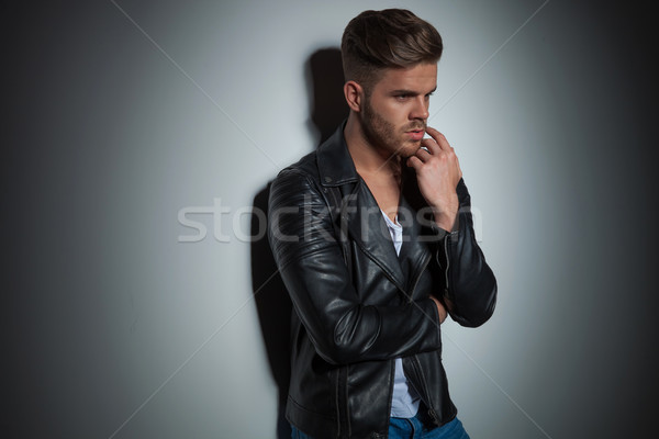 portrait of pensive young man wearing leather jacket standing Stock photo © feedough