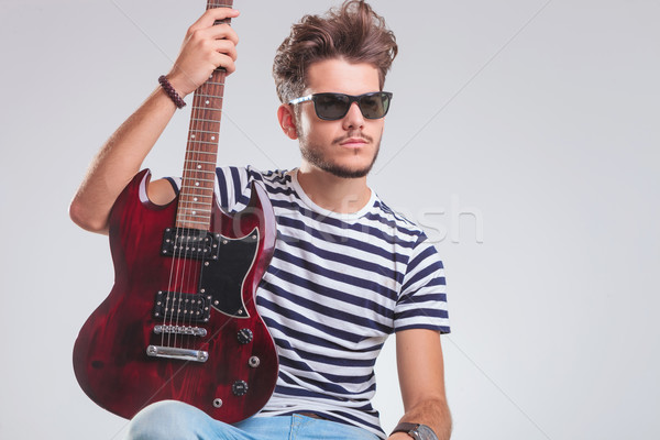 Stock photo: artist pose seated in studio with guitar, looking away