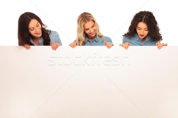 Três feliz mulheres olhando para baixo grande conselho Foto stock © feedough