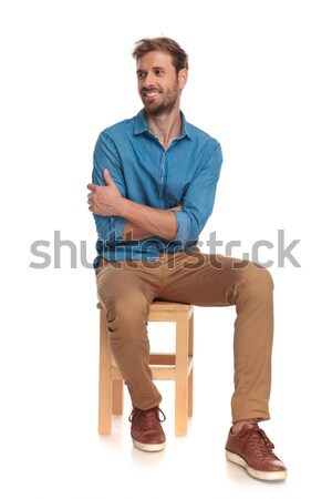 smiling seated young casual man looks to side Stock photo © feedough
