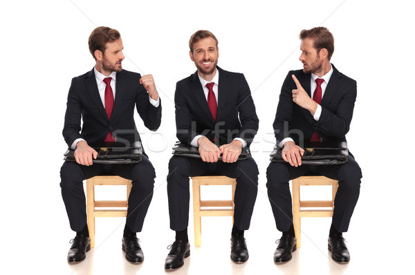 young businessman fighting with himself while sitting Stock photo © feedough