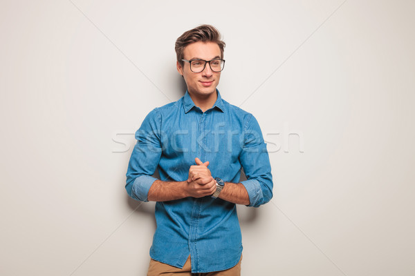 young casual man wearing glasses holding palms together Stock photo © feedough