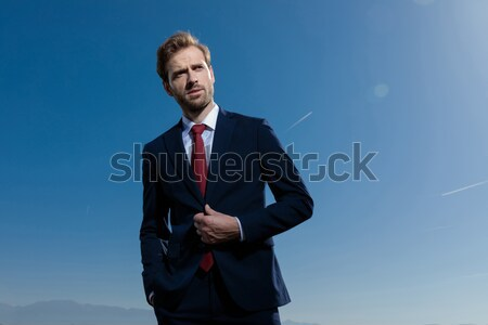 portrait of a handsome elegant man buttoning his burgundy suit  Stock photo © feedough