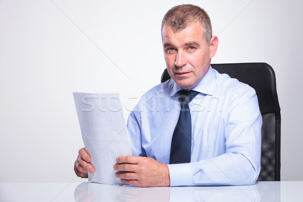 old business man sits at desk with documents Stock photo © feedough