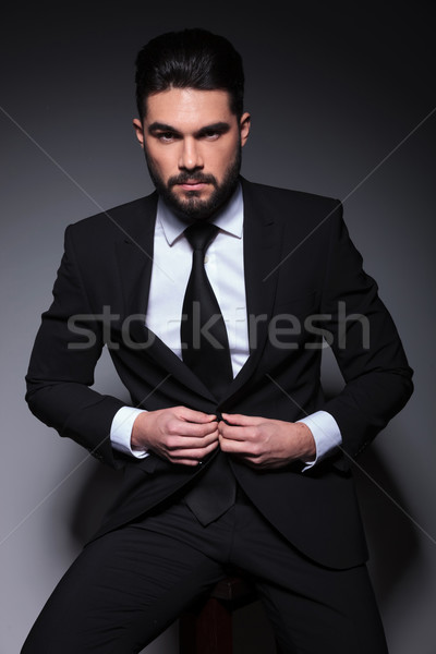 Stock photo: young fashion man looks at you and buttons suit