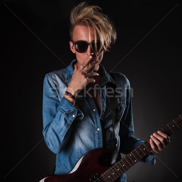 cool guitarist smoking his cigarette in studio  Stock photo © feedough
