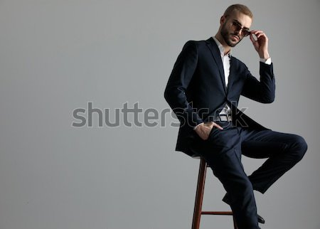 Jonge man smoking vergadering Open jas grijs Stockfoto © feedough