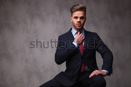portrait of seated young businessman in tuxedo fixing his bowtie Stock photo © feedough