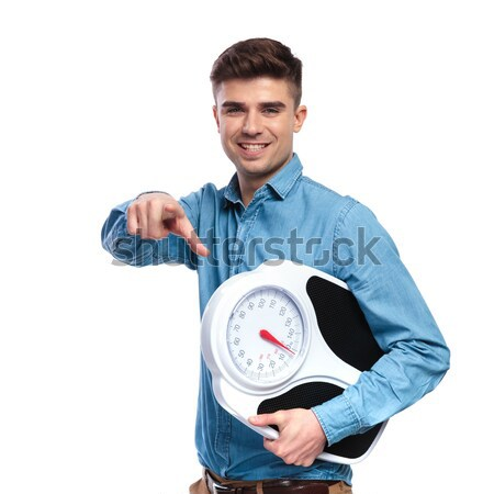 healthy casual man holding a scale and smiles Stock photo © feedough