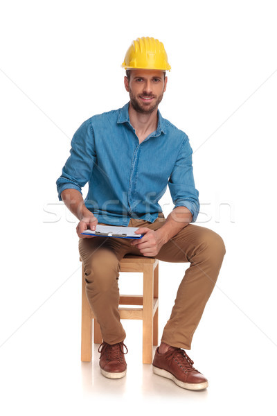 young seated construction engineer with clipboard Stock photo © feedough