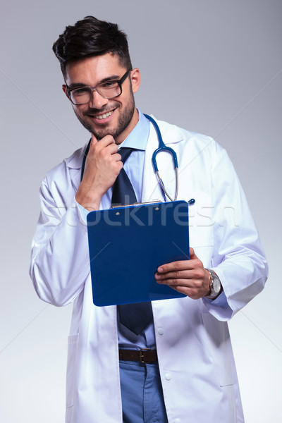 young doctor with clipboard touches his chin and smiles Stock photo © feedough