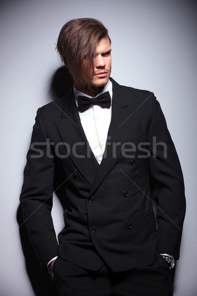 Fiatal elegáns férfi öltöny csokornyakkendő másfelé néz Stock fotó © feedough
