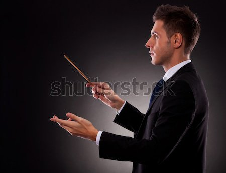 Back view of a young composer directing with his baton Stock photo © feedough