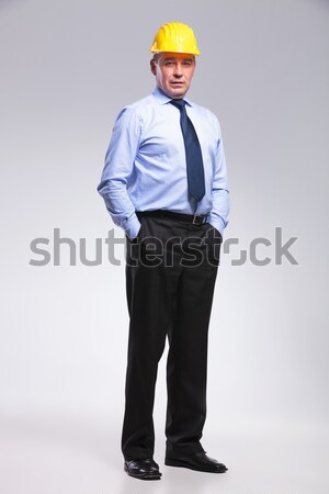 old engineer with helmet and hands in pocket Stock photo © feedough