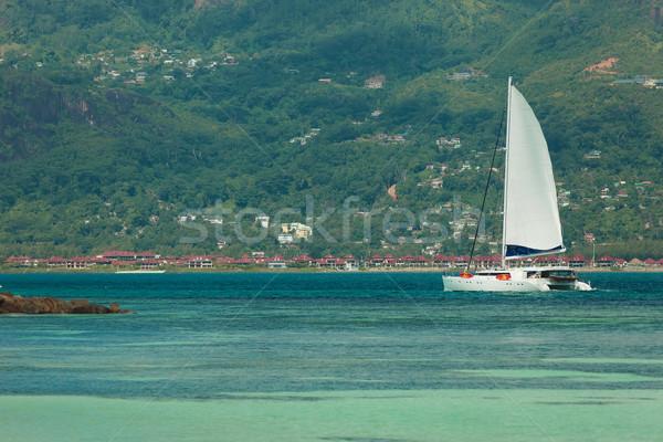 sailing through blue clear water next to a mountain  Stock photo © feedough