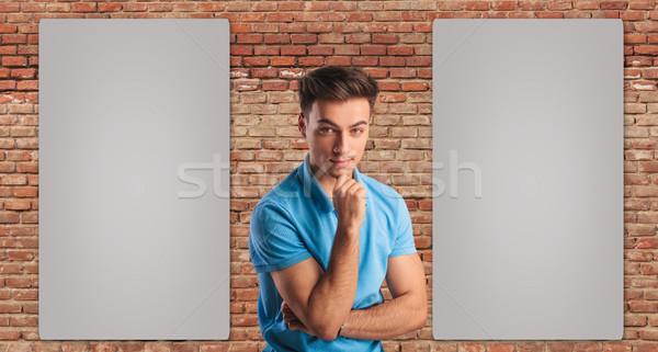 Giovani casuale uomo pensare due cartelloni pubblicitari Foto d'archivio © feedough