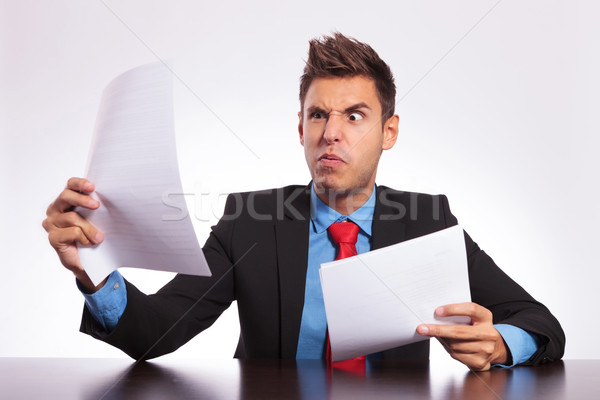 Stock photo: confused man reading at desk