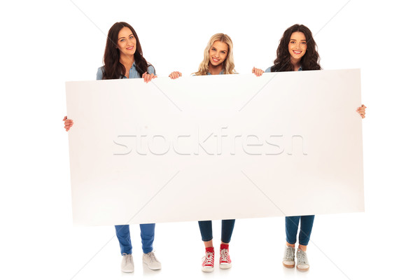 full body picture of three  casual women holding big billboard Stock photo © feedough
