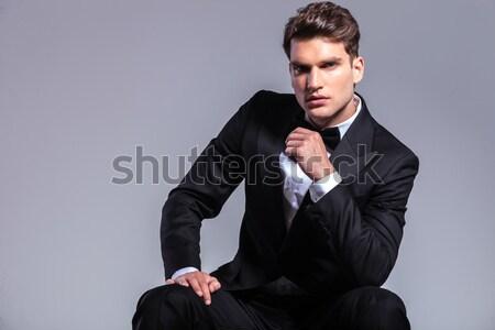 potrait of pensive young man in black tuxedo sitting Stock photo © feedough