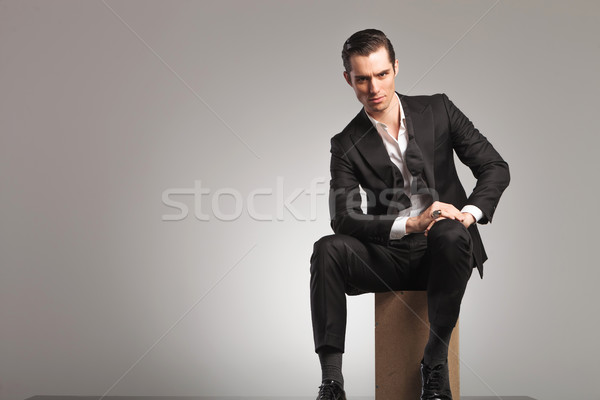 elegant man sitting on wooden box with undone bowtie Stock photo © feedough
