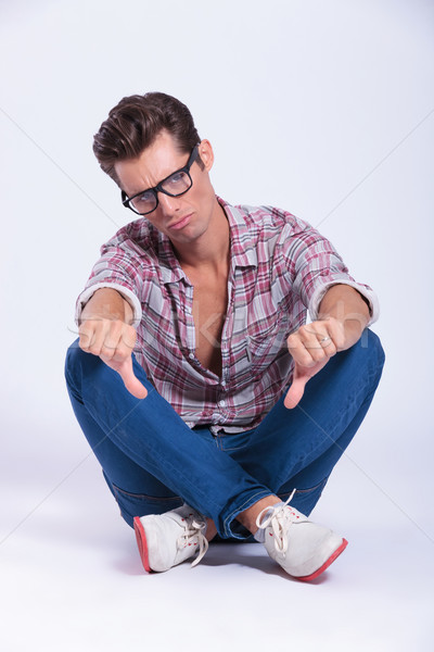 casual man sits and shows thumbs down Stock photo © feedough