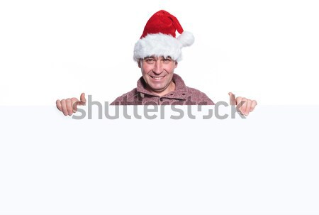 Stock photo: mature casual man in santa hat is holding a big blank board