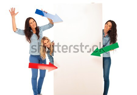 three young women pointing arrows to a big blank board  Stock photo © feedough