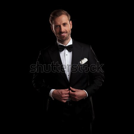 smiling young elegant man in tuxedo buttoning his coat Stock photo © feedough