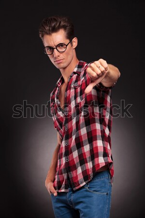 handsome young man with thumbs down Stock photo © feedough
