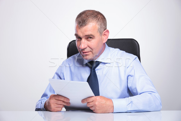 old business man at desk holds papers Stock photo © feedough