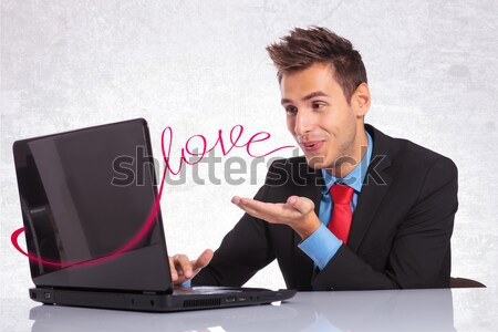 young business man cheers while reading on laptop Stock photo © feedough