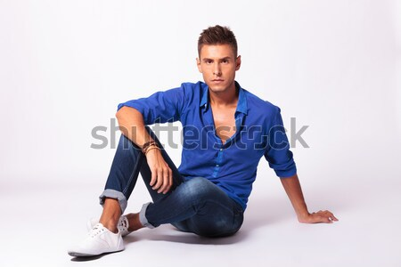smiling man in denim shirt sitting legs crossed in studio backgr Stock photo © feedough