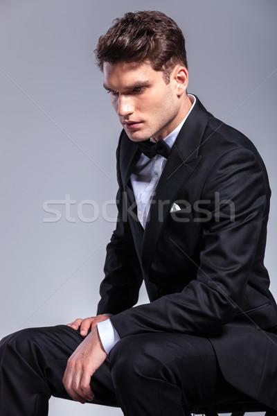 Uomo d'affari guardando verso il basso seduta vista laterale giovani elegante Foto d'archivio © feedough