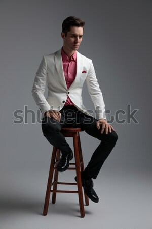 sensual young man posing seated on stool in studio Stock photo © feedough