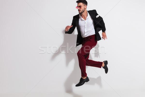 Jóképű férfi visel fekete öltöny ugrik levegő piros Stock fotó © feedough