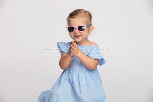 happy little girl in blue dress and sunglasses is clapping Stock photo © feedough