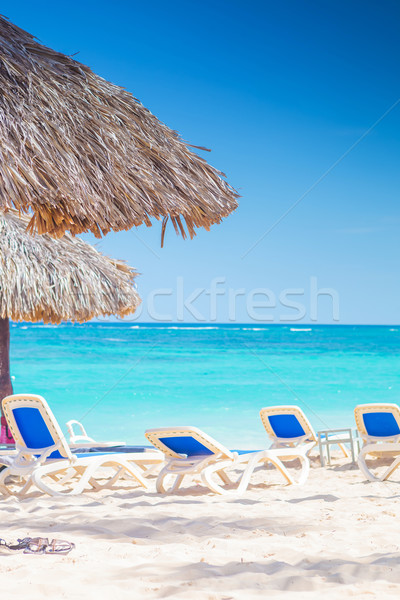 chairs and straw umbrellas on stunning tropical beach Stock photo © feedough