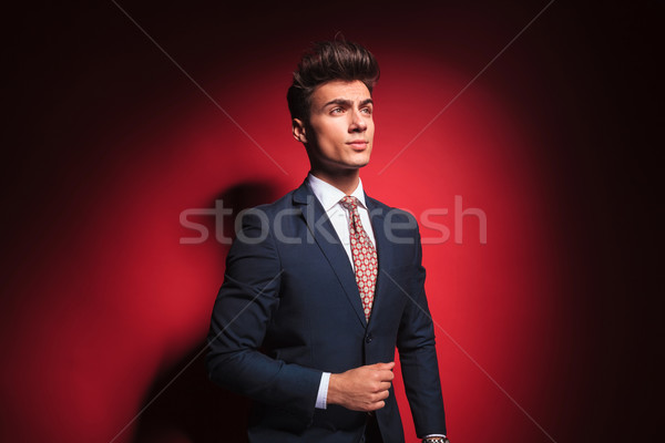 young businessman in black with red tie arranging his jacket Stock photo © feedough