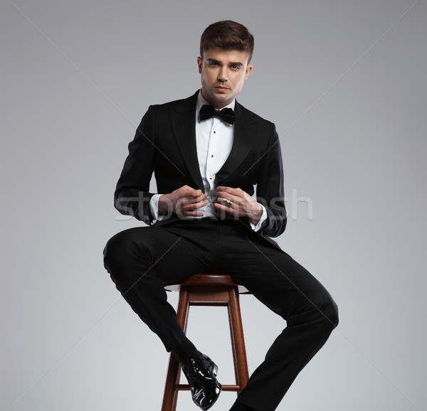 seductive young man sitting and buttoning his black suit jacket Stock photo © feedough