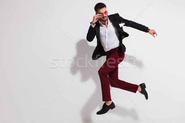 side view of jumping smart casual man fixing his sunglases Stock photo © feedough