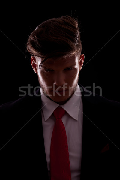 Figure of elegant young business man posing in darkness, looking with an angry expression into the c Stock photo © feedough