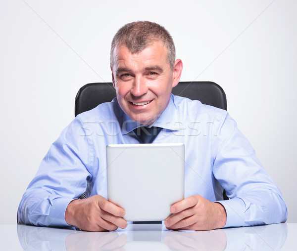 old business man at desk holds his tablet Stock photo © feedough