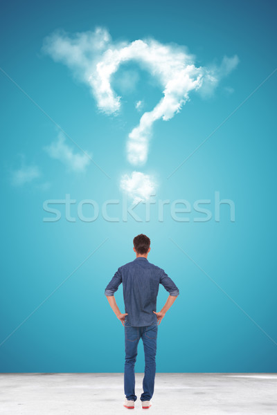 casual young man looking at a big question mark made of clouds Stock photo © feedough