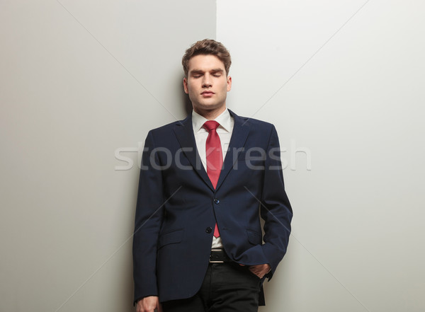 business man leaning on a wall with his eyes closed Stock photo © feedough