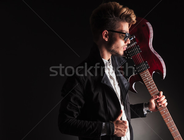 cool young guitarist holding his electric guitar on shoulder Stock photo © feedough