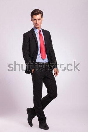 elegant man in suit and undone bowtie sitting on chair Stock photo © feedough