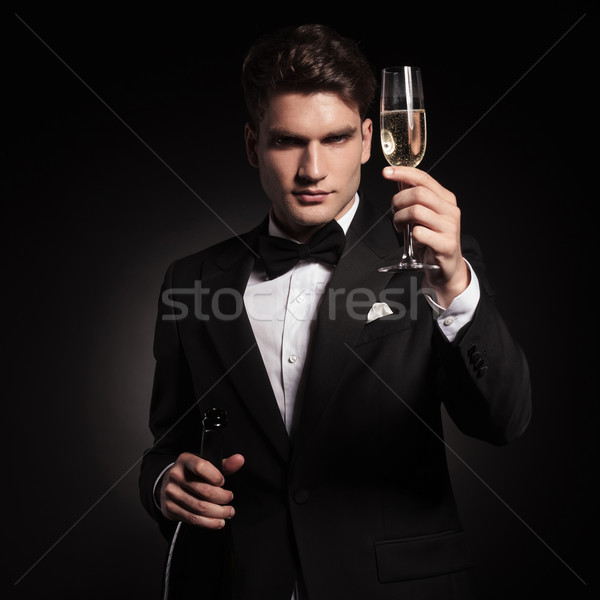 elegant man holdinh up a glass of champagne. Stock photo © feedough